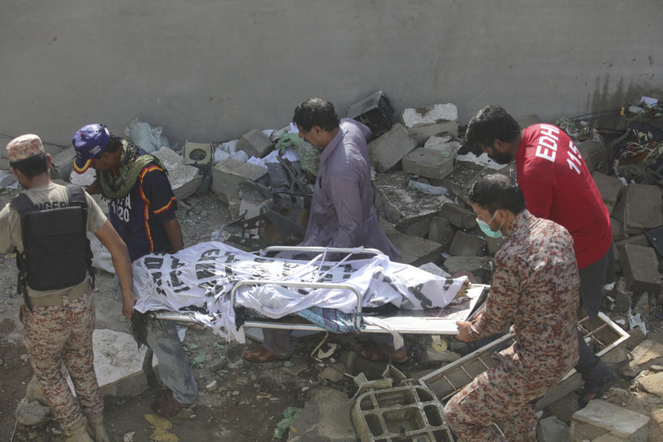 Volunteers carry the dead body of plane crash victim in Karachi, Pakistan, Friday, May 22, 2020. An aviation official says a passenger plane belonging to state-run Pakistan International Airlines carrying more than 100 passengers and crew has crashed near the southern port city of Karachi. (AP Photo/Fareed Khan)