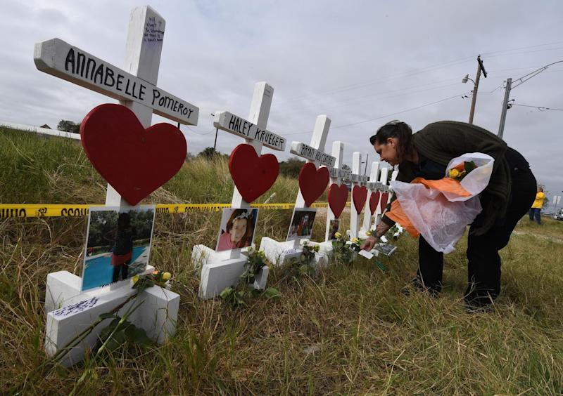 Jessica Mires leaves flowers on crosses named for the victims outside the First Baptist Church, where a mass shooting that killed 26 people: MARK RALSTON/AFP/Getty Images