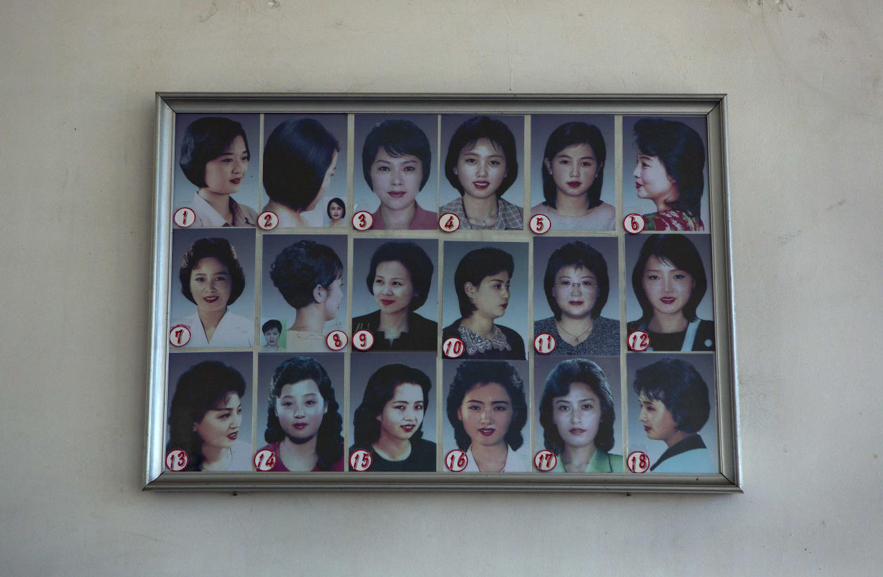 Photos showing example hair styles hang inside a hair salon in Pyongyang, North Korea on Wednesday, Feb. 20, 2013. (AP Photo/David Guttenfelder)