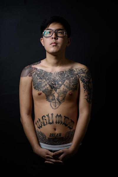 Suh Hyun-Woong, 19, displays his tattoos inked by Jang Jun-Hyuk as he poses for a photo at the Tattooism tattoo studio in Seoul on November 21, 2014 (AFP Photo/Ed Jones)