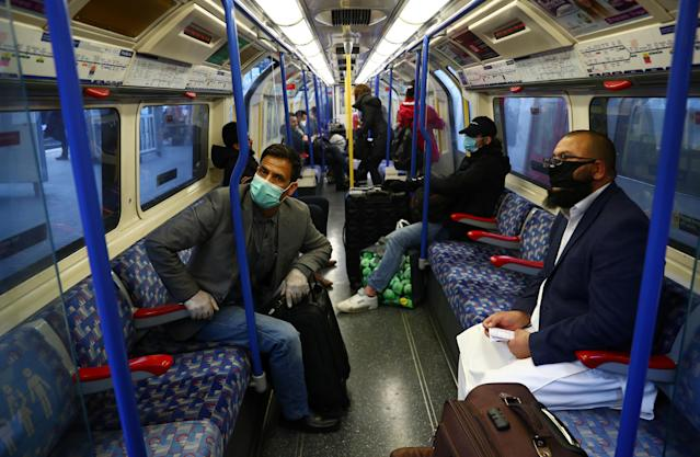 Commuters wear protective face masks on a Piccadilly line train on the London Underground. (Reuters)
