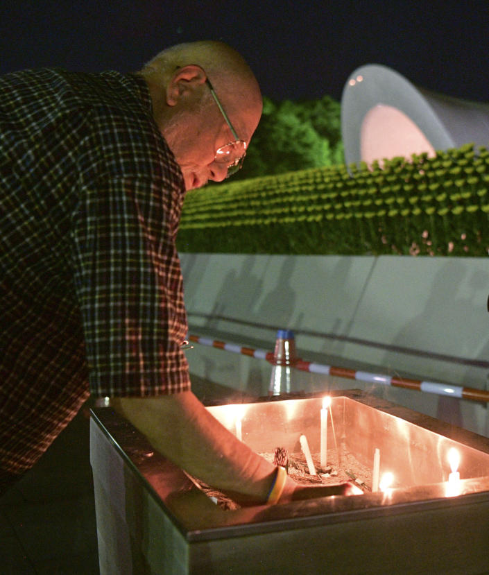 A man burns a stick of incense at the cenotaph dedicated to the victims of atomic bombing at Hiroshima Peace Memorial Park in Hiroshima, western Japan, early Monday, Aug. 6, 2018, marking the 73rd anniversary of the bombing. (Yohei Nishimura/Kyodo News via AP)