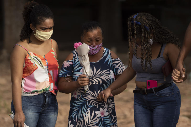 """Maria Francisca dos Santos, center, attends the burial of her 57-year-old husband,  Paulo Jose da Silva, who died from the new coronavirus, in Rio de Janeiro, Brazil, Friday, June 5, 2020. According to Monique dos Santos, right, her stepfather mocked the existence of the virus, didn't use a mask, didn't take care of himself, and wanted to shake hands with everybody. """"He didn't believe in it and unfortunately he met this end. It's very sad, but that's the truth,"""" she said. (AP Photo/Leo Correa)"""