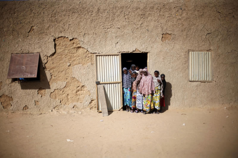 In this picture taken Monday Feb. 18, 2013, children gather at the door of Mohamed Salia's madrassa in Gao, northern Mali. Nearly a month after the al-Qaida-linked militants were driven out of Gao and into the surrounding villages, students are now returning to the city's Quranic schools. Many classrooms, though, are still half full, as tens of thousands of people fled the fighting and strict Islamic rule imposed by the extremists. (AP Photo/Jerome Delay)
