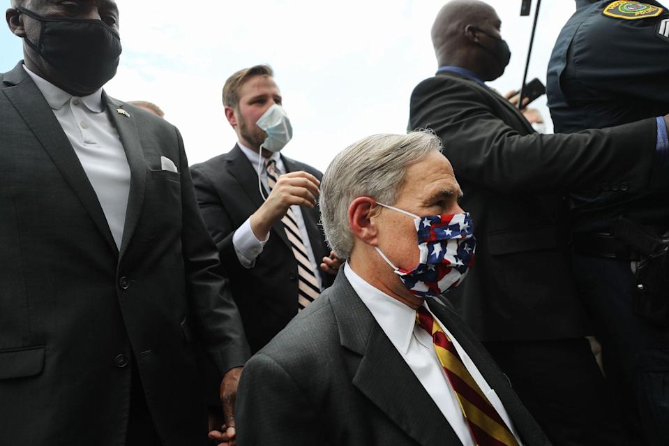 Texas Gov. Greg Abbott (Center R) approaches the line for people to attend the public viewing for George Floyd outside the Fountain of Praise church on June 8, 2020 in Houston, Texas.
