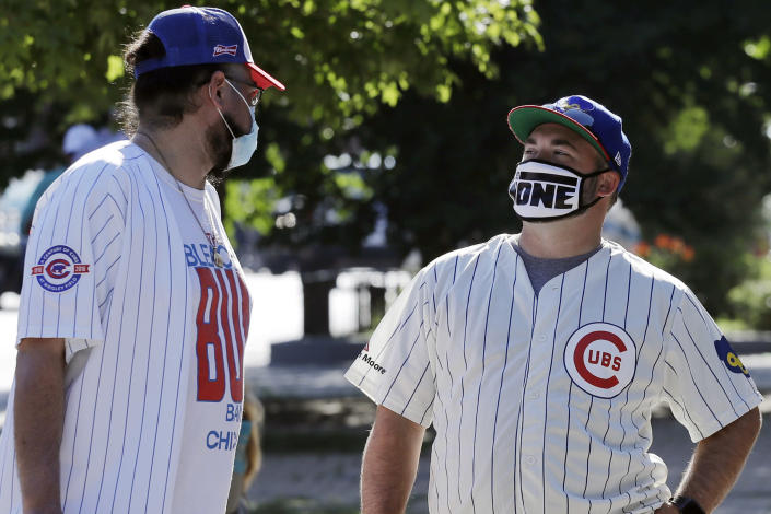 **Photo holds for Jordan Cohen's story** Chicago Cubs fans wait for a ball outside of Wrigley Field before the Opening Day baseball game between the Chicago Cubs and the Milwaukee Brewers in Chicago, Friday, July 24, 2020, in Chicago. The Chicago Cubs open against the Milwaukee Brewers. In a normal year, that would mean a sellout crowd at Wrigley Field and jammed bars surrounding the famed ballpark. But in a pandemic-shortened season, it figures to be a different atmosphere. (AP Photo/Nam Y. Huh)