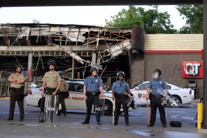 FILE - In this Aug. 11, 2014, file photo, police wearing riot gear stand outside a convenience store that was burned and looted in Ferguson, Mo. The FBI opened an investigation into Brown's death, and two men who said they saw the shooting told reporters that Brown had his hands raised when the officer approached with his weapon and fired. (AP Photo/Jeff Roberson, File)
