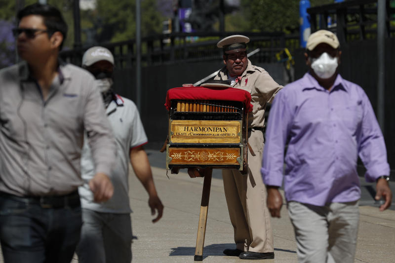 "Organ grinder Moises Rosas solicits tips from pedestrians in central Mexico City, Tuesday, March 24, 2020. Rosas, who has been an organ grinder for 25 years, says he isn't afraid of the new coronavirus and needs the average of 200 pesos (around $8.50) he takes home per day. ""We live from day to day, so if we don't work, there won't be income for the house, the family."" (AP Photo/Rebecca Blackwell)"