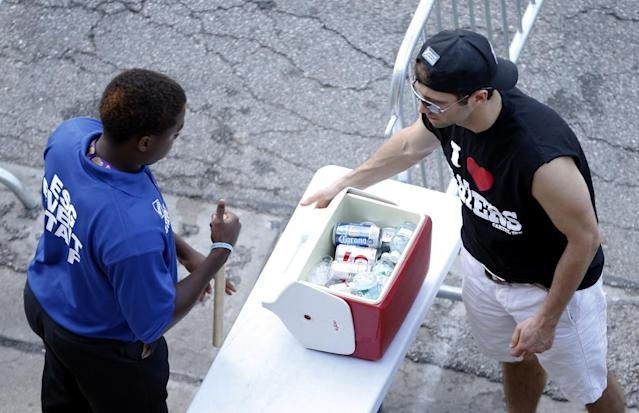 A fan's cooler is inspected as he makes his way though a security checkpoint to enter the Indianapolis Motor Speedway before the start of the 98th running of the Indianapolis 500 IndyCar auto race in Indianapolis, Sunday, May 25, 2014. (AP Photo/AJ Mast)