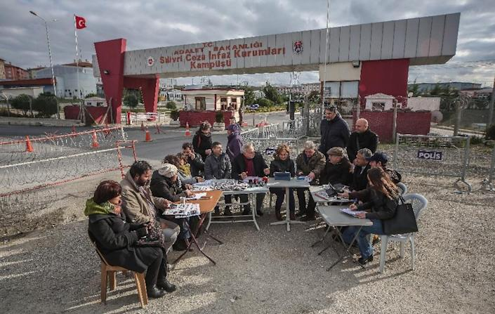 This picture taken and released by the Cumhuriyet daily newspaper on December 15, 2015 shows Cumhuriyet's journalists doing their editorial news meeting next to the Silivri prison, to demonstrate their support for their jailed editor in-chief (AFP Photo/)