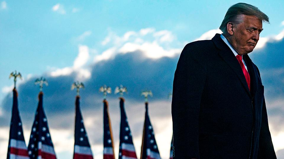 Donald Trump in front of US flags.
