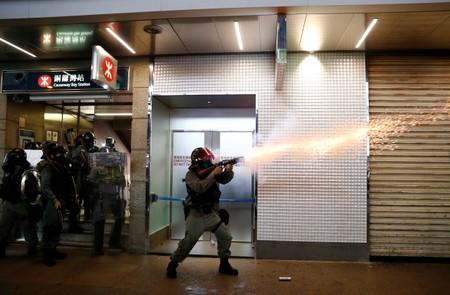 A riot police officer fires a tear gas canister during a rally in Central, Hong Kong