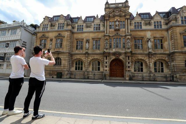 Passers-by photograph the Rhodes statue at Oriel College