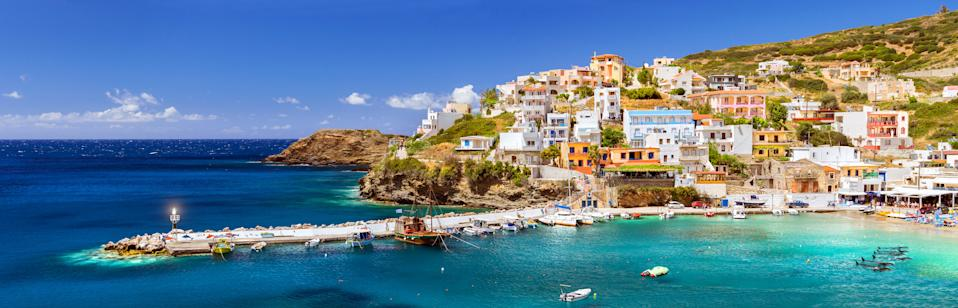 Crete, Greece. Harbour with marine vessels, boats and lighthouse. View from cliff on Bay with beach and architecture Bali - vacation destination resort with clear ocean water, Rethymno