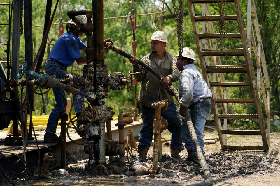 Oil well workers prepare to plug an orphaned well on the Rooke family ranch, Tuesday, May 18, 2021, near Refugio, Texas. Oil and gas drilling began on the ranch in the 1920s and there were dozens of orphaned wells that needed to be plugged for safety and environmental protection. (AP Photo/Eric Gay)