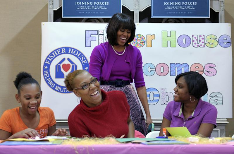 First lady Michelle Obama shares a laugh with, from left, Sanae Bright, Kerry Bright and Ashanti Ferguson, during her visit to the Fisher House, located at Walter Reed National Military Medical Center in Bethesda, Md., Wednesday, March 20, 2013, for a pre-Easter celebration with military families and children. (AP Photo/Susan Walsh)