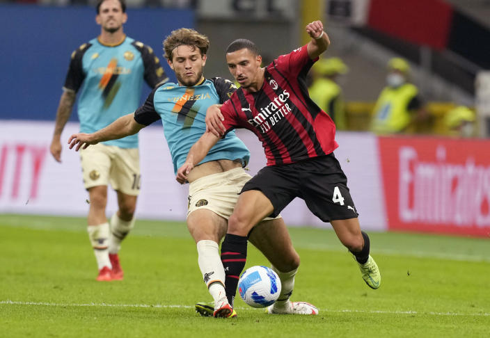Venezia's Tanner Tessmann, left, challenges for the ball with AC Milan's Ismael Bennacer during the Serie A soccer match between AC Milan and Venezia at the San Siro stadium, in Milan, Italy, Wednesday, Sept. 22, 2021. Italian soccer team Venezia is back in the top division for the first time since 2002. And it has tapped Major League Soccer to recruit young Americans in its bid to stay afloat in Serie A. Nineteen-year-old Gianluca Busio arrived in Venice from Sporting Kansas City and 20-year-old Tanner Tessmann from FC Dallas. (AP Photo/Antonio Calanni)