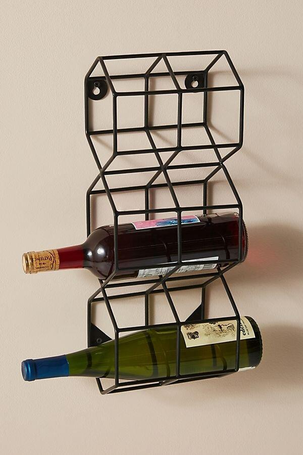 """<p>Sort out your wine stash and make use of wall space with this wall-mounted wine rack that can hold three of your favorite bottles. Choose from bronze or black to match your kitchen decor. </p> <p><strong>To buy: </strong>$48, <a href=""""https://click.linksynergy.com/deeplink?id=93xLBvPhAeE&mid=39789&murl=https%3A%2F%2Fwww.anthropologie.com%2Fshop%2Fthea-wall-mounted-wine-rack2%3F&u1=RS%2CAnthropologieJustLaunchedMoreThan1%252C700NewHomeItems%25E2%2580%2594Our5FavoritesUnder%252450%2Ckholdefehr1271%2CDEC%2CIMA%2C691325%2C202001%2CI"""" rel=""""nofollow noopener"""" target=""""_blank"""" data-ylk=""""slk:anthropologie.com"""" class=""""link rapid-noclick-resp"""">anthropologie.com</a>. </p>"""