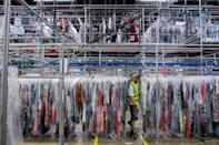 "A person moves through clothing in the storage area at Rent the Runway's ""Dream Fulfillment Center"" in Secaucus, New Jersey"