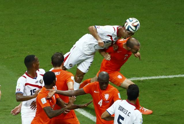 Costa Rica's Giancarlo Gonzalez jumps for the ball next to Ron Vlaar of the Netherlands during their 2014 World Cup quarter-finals at the Fonte Nova arena in Salvador July 5, 2014. REUTERS/Ruben Sprich (BRAZIL - Tags: SOCCER SPORT WORLD CUP)