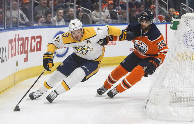 Nashville Predators' Ryan Johansen (92) and Edmonton Oilers' Darnell Nurse (25) battle for the puck during first-period NHL hockey game action in Edmonton, Alberta, Saturday, Feb. 8, 2020. (Jason Franson/The Canadian Press via AP)