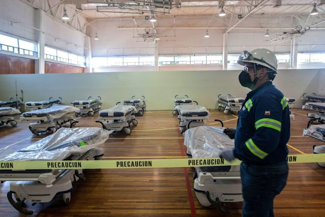 """Workers convert the gym of the steel company Ternium into a field hospital for COVID-19 patients in Monterrey, Mexico. <span class=""""copyright"""">(AFP via Getty Images)</span>"""