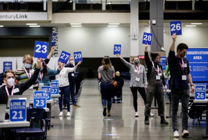 Workers hold up their station signs to signal they are ready for a patient as people attend a coronavirus disease (COVID-19) vaccination site at Lumen Field Event Center in Seattle