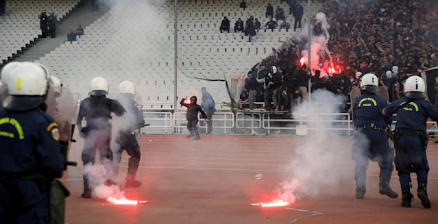 Soccer Football - Greek Cup Final - AEK Athens vs PAOK Salonika - Athens Olympic Stadium, Athens, Greece - May 12, 2018 Police look on while flares are on the ground before the match REUTERS/Alkis Konstantinidis