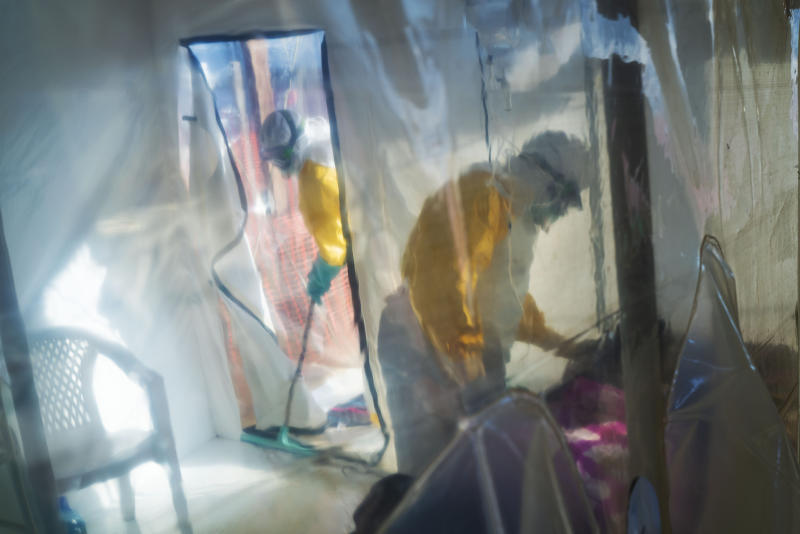 In this photograph taken Saturday 13 July 2019, health workers wearing protective suits tend to to an Ebola victim kept in an isolation cube in Beni, Congo DRC. The Congolese health ministry is confirming the country's first Ebola case in the provincial capital of 2 million, Goma, some 360 kms ( 225 miles) south of Beni. More than 1,600 people in eastern Congo have died as the virus has spread in areas too dangerous for health teams to access. (AP Photo/Jerome Delay)