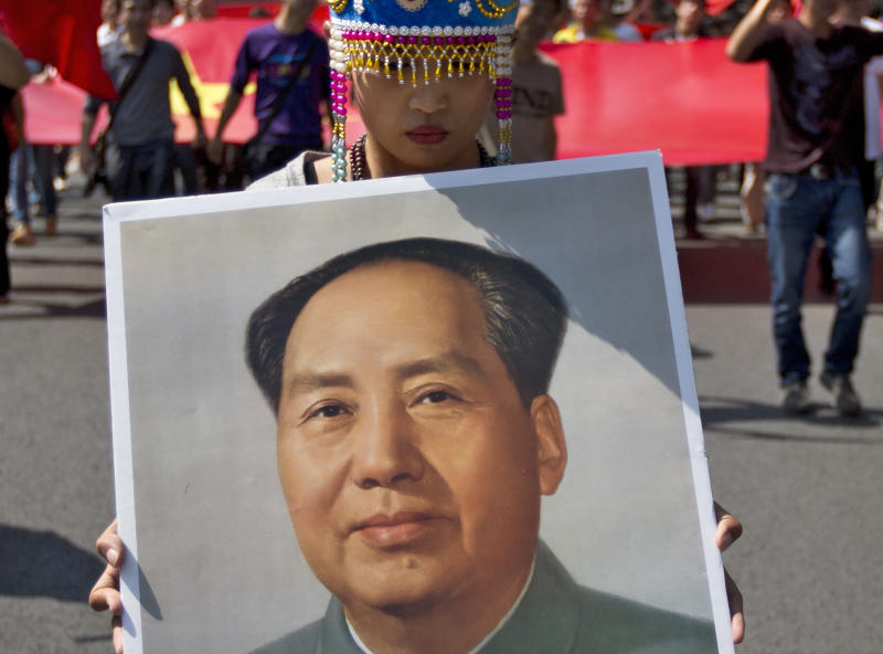 In this photo taken on Sunday, Sept. 16, 2012, a female demonstrator dressed in a traditional costume holds a picture of the late Communist leader Mao Zedong while marching with others during an anti-Japan protest outside the Japanese Embassy in Beijing. The face of dissatisfaction with China's Communist Party is the face of the man synonymous with it: Mao Zedong. Portraits of the revolutionary leader, hoisted by people born after his death 36 years ago, often led packs of demonstrators in protests over Japan's effort last week to bolster its hold on islands claimed by China. (AP Photo/Andy Wong)