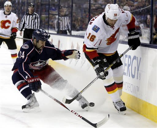 Columbus Blue Jackets' Derek MacKenzie, left, works for the puck against Calgary Flames' Brian McGrattan in the first period of an NHL hockey game in Columbus, Ohio, Friday, March 22, 2013. (AP Photo/Paul Vernon)