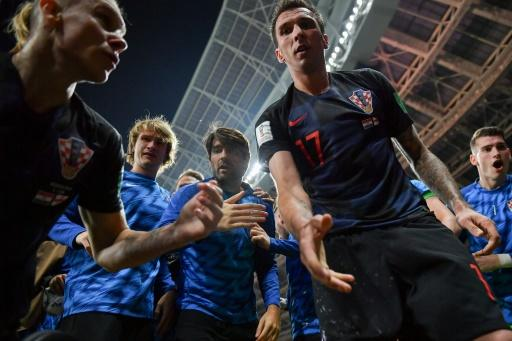 Hand it to Yuri! Croatia's Mario Mandzukic offers to help AFP photographer Yuri Cortez after he fell on him with teammates while celebrating their second goal against England