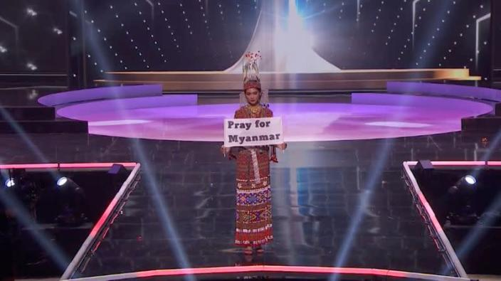 """Ma Thuzar Wint Lwin, Miss Universe Myanmar, holds the """"Pray for Myanmar"""" sign during Miss Universe pageant's national costume show, in Hollywood"""