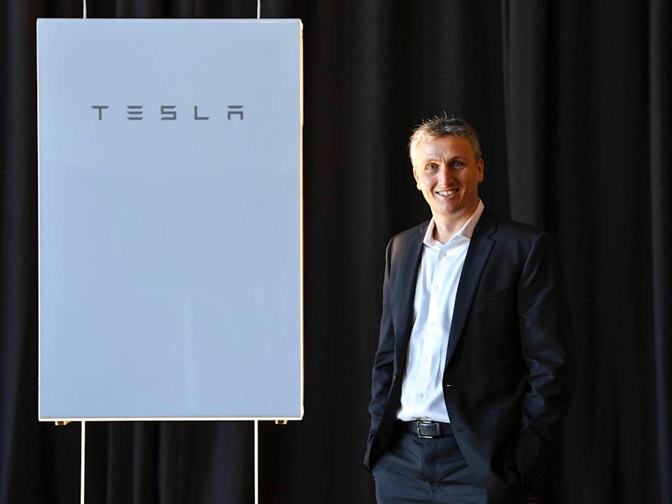 SolarCity cofounder Lyndon Rive standing by a Tesla Powerwall battery.