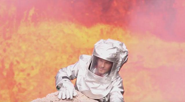 Canadian adventurer George Kourounis, wearing a fire proof suit, climbing out of the crater. Photo: Bradley Ambrose
