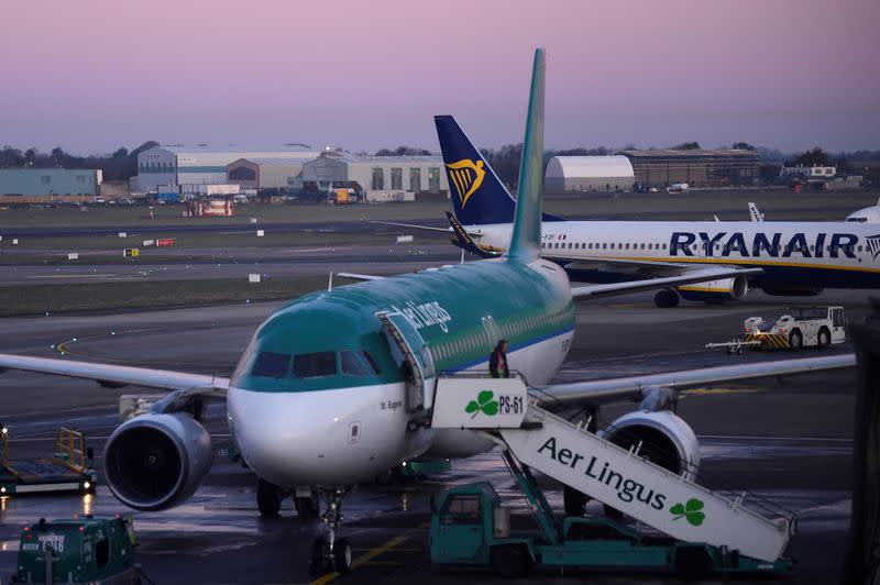 FILE PHOTO: Passengers disembark from Aer Lingus and Ryanair aircraft at Dublin airport at dawn in Dublin