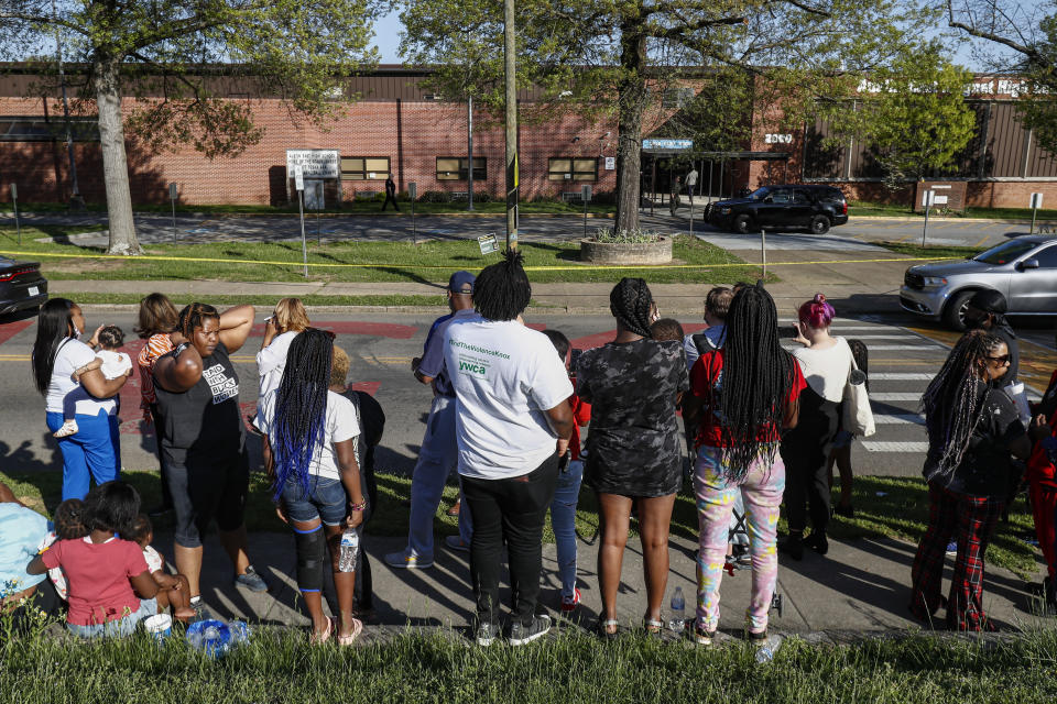 People look on as Knoxville police work the scene of a shooting at Austin-East Magnet High School Monday, April 12, 2021, in Knoxville, Tenn. (AP Photo/Wade Payne)