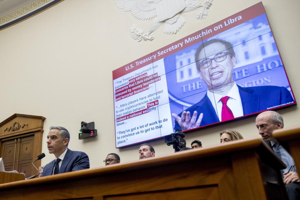 Quotes from Treasury Secretary Steve Mnuchin are displayed on a screen behind David Marcus, CEO of Facebook's Calibra digital wallet service, left, as he speaks during a House Financial Services Committee hearing on Facebook's proposed cryptocurrency on Capitol Hill in Washington, Wednesday, July 17, 2019. (AP Photo/Andrew Harnik)