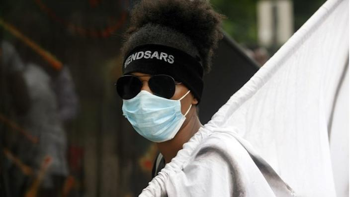 A protester wears a face mask and a head band with the inscription