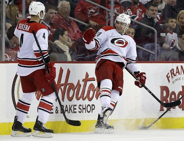 Carolina Hurricanes right wing Patrick Dwyer, right, celebrates with teammate Andrej Sekera, of Slovakia, after scoring a goal on the New Jersey Devils during the second period of an NHL hockey game on Wednesday, Nov. 27, 2013, in Newark, N.J. (AP Photo/Julio Cortez)