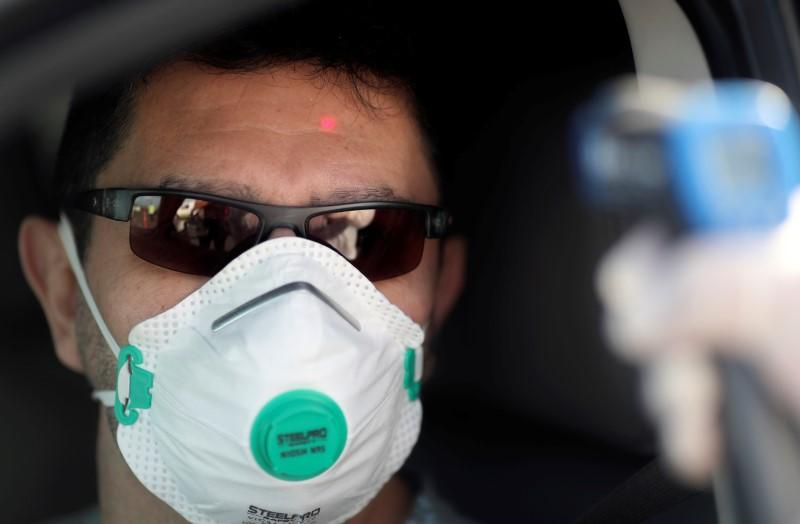 A health worker takes the temperature of a driver for precaution due to coronavirus disease (COVID-19), in Buenos Aires