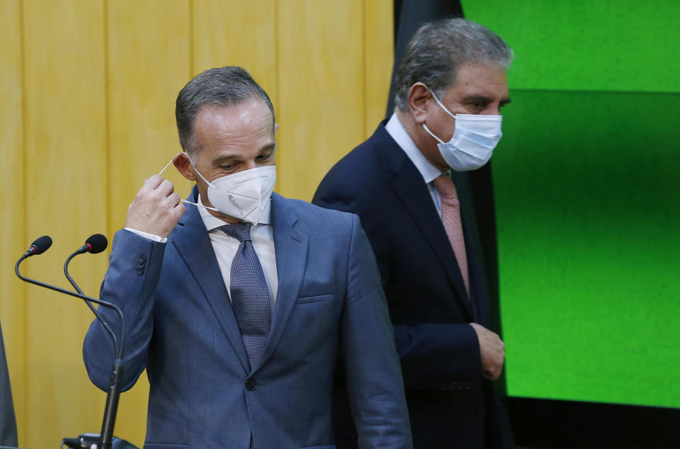 German Foreign Minister Heiko Maas, front, removes mask while his Pakistani counterpart Shah Mahmood Qureshi walks towards his standing position for a press conference after their meeting in Islamabad, Pakistan, Tuesday, August 31, 2021. Maas arrived in Islamabad on a two-day visit to hold talks with Pakistani leadership to discuss bilateral matters, international issues and the current situation in Afghanistan. (AP Photo/Anjum Naveed)