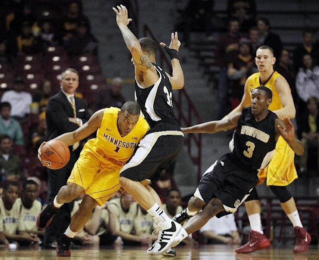 Minnesota guard Andre Hollins (1) pushes the ball around Wofford forward Lee Skinner, second from left, in the first half of an NCAA college basketball game Thursday, Nov. 21, 2013, in Minneapolis. (AP Photo/Stacy Bengs)