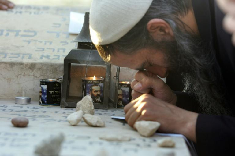Candles burn with the image of the late rabbi Meir Kahane as a follower prays at his grave in 2006