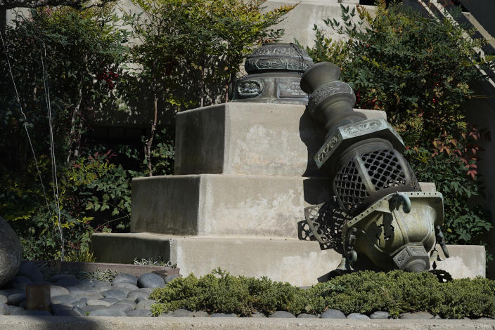 One of a pair of metal lanterns knocked down at the entrance of the Higashi Honganji Buddhist Temple, is seen in Los Angeles Saturday, Feb. 27, 2021. Surveillance video caught a man jumping the security fences at the Higashi Honganji Buddhist Temple on Thursday night, smashing a 12-foot-high glass window with a rock, yanking a pair of metallic lanterns off their concrete bases and lighting two wooden lantern stands on fire, the temple's head priest told the Los Angeles Times. (AP Photo/Damian Dovarganes)