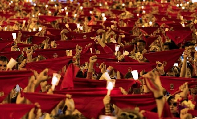 Revellers raise red scarves and candles as they sing the song 'Pobre de Mi', marking the end of the San Fermin festival in Pamplona, northern Spain (AFP Photo/JAIME REINA)