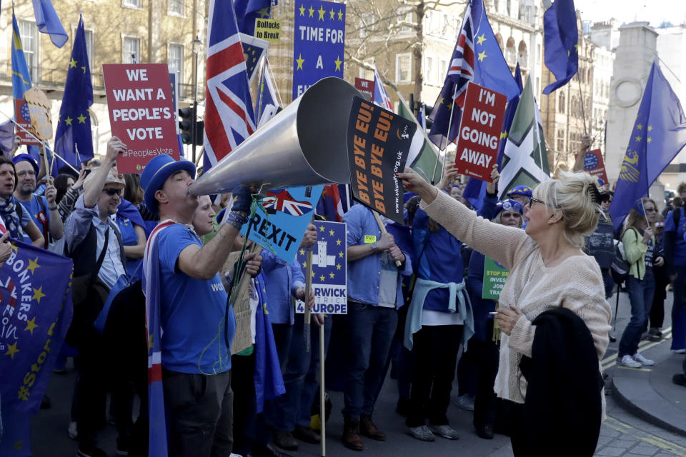 FILE - In this Wednesday, Feb. 27, 2019 file photo, a Brexit supporter, at right, holds a placard up in front of remain in the EU supporters protesting outside Downing Street in London. Britain and the European Union have struck a provisional free-trade agreement that should avert New Year's chaos for cross-border commerce and bring a measure of certainty to businesses after years of Brexit turmoil. The breakthrough on Thursday, Dec. 24, 2020 came after months of tense and often testy negotiations that whittled differences down to three key issues: fair-competition rules, mechanisms for resolving future disputes and fishing rights. (AP Photo/Matt Dunham, File)