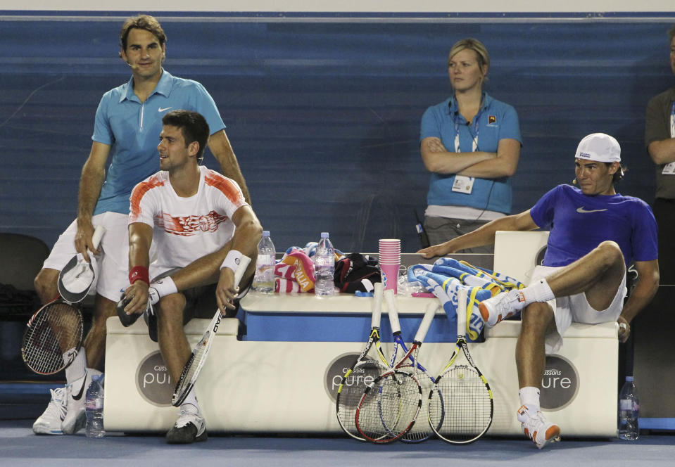 FILE - Roger Federer of Switzerland, left, Novak Djokovic of Serbia, second left, and Rafael Nadal of Spain watch an exhibition tennis match in Melbourne, Australia, in this Sunday Jan. 17, 2010, file photo. Novak Djokovic, Rafael Nadal and Roger Federer all ended up in the same half of the French Open men's field in the draw Thursday, May 27, 2021, meaning no more than one of them can reach the final. (AP Photo/Mark Baker, File)