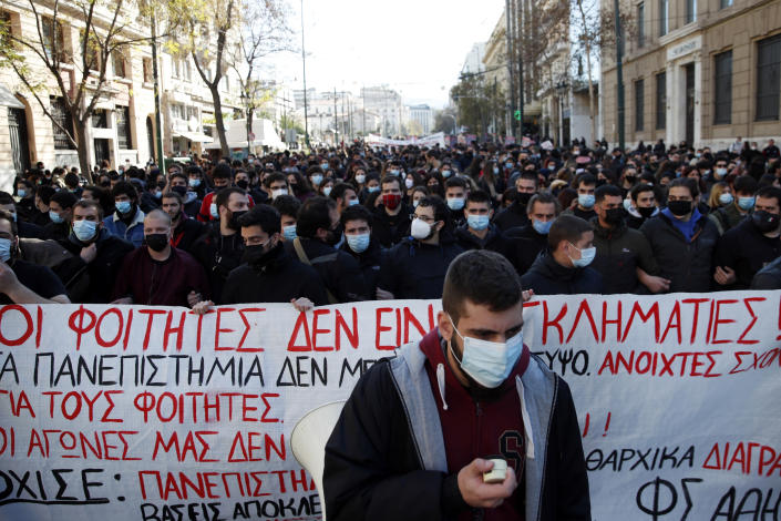"University students gather during a rally against educational reforms as the banner reads ""The students are not criminals"" in Athens, Thursday, Jan. 21, 2021. About 1,500 students took part in two separate protests against government's plans to set up a state security division at university campuses and time limits set for the completion of degree courses. (AP Photo/Thanassis Stavrakis)"