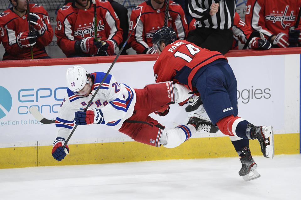 Washington Capitals right wing Richard Panik (14) collides with New York Rangers defenseman Libor Hajek (25) during the third period of an NHL hockey game, Sunday, March 28, 2021, in Washington. (AP Photo/Nick Wass)